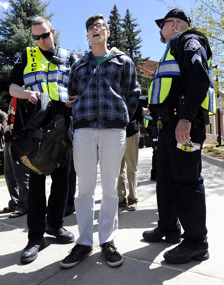 Photo -   University of Colorado senior Jonathan Edwards is arrested by Boulder County Sheriff deputies for trespassing on Norlin Quad by going past the police tape on the University of Colorado campus in Boulder, Colo., on Friday, April 20, 2012. A block-long line of protesters marched onto the University of Colorado, testing the school's determination to push the annual April 20 marijuana celebration off campus. (AP Photo/The Daily Camera, Jeremy Papasso)