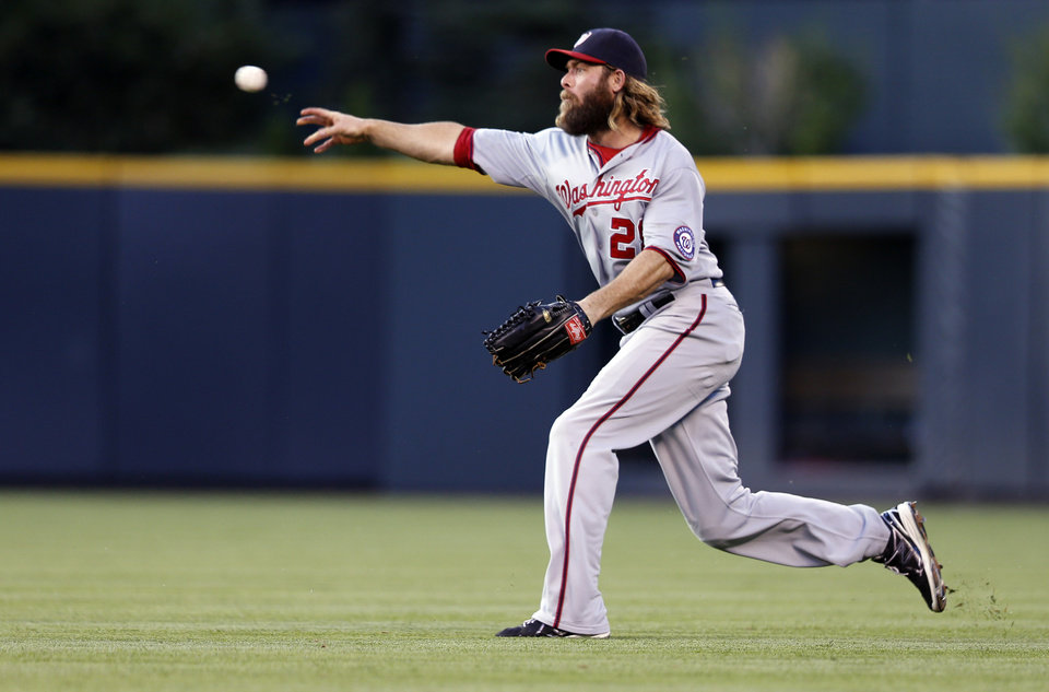 Photo - Washington Nationals right fielder Jayson Werth unsuccessfully throws to second to out Colorado Rockies' DJ LeMahieu after second baseman Danny Espinosa dropped a fly ball during the second inning of a baseball game on Monday, July 21, 2014, in Denver. (AP Photo/Jack Dempsey)