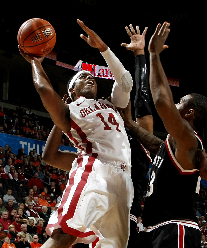 Photo - OU's Carl Blair Jr. puts up a shot beside Cincinnati's Sean Kilpatrick during the All-College Classic basketball game between the University of Oklahoma and Cincinnati at the Oklahoma City Arena on Saturday, December 18,  2010.   Photo by Bryan Terry, The Oklahoman