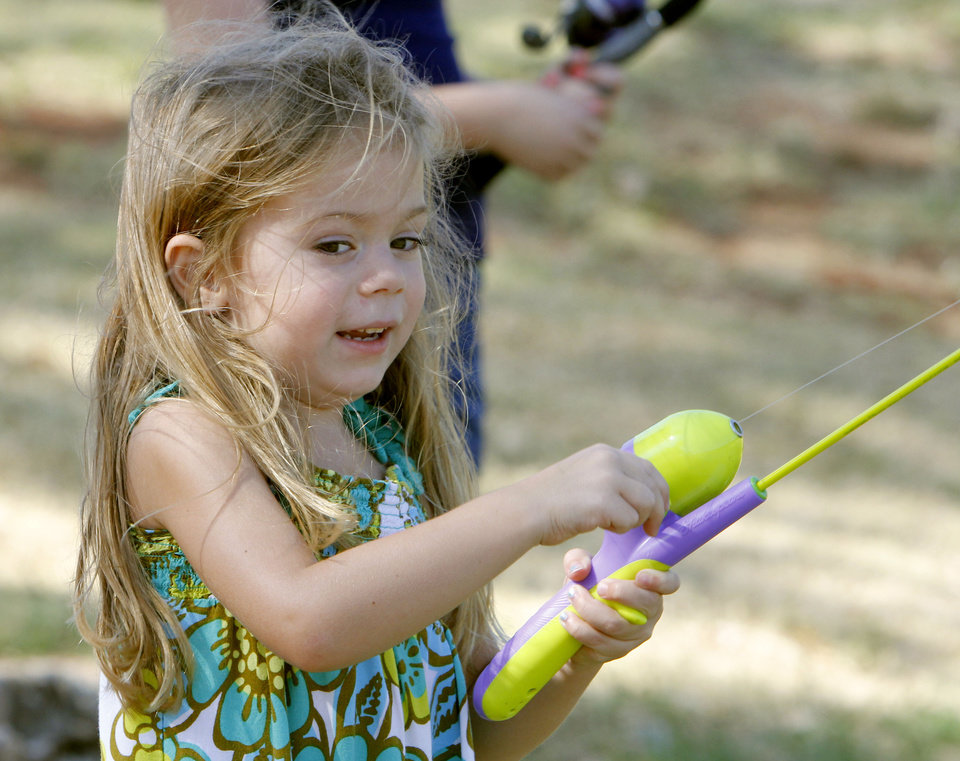 Four year old Madalyn Rhoads reals in a fish during a fishing derby at Little River Park in Moore, OK, Saturday, August 4, 2012,  By Paul Hellstern, The Oklahoman