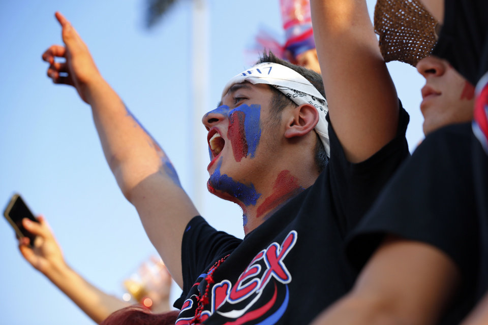 Photo - Moore fan Bryce Ludwic yells as Westmoore plays Moore High School on Friday, Sept. 6, 2013 in Moore, Okla.  Photo by Steve Sisney, The Oklahoman