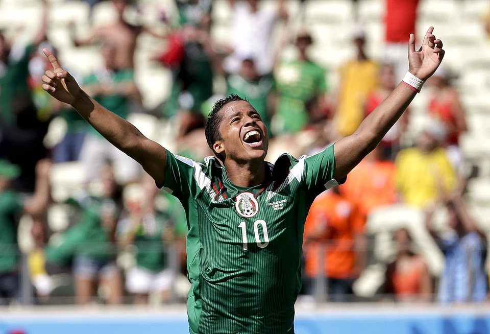 Photo - Mexico's Giovani dos Santos celebrates after scoring his side's first goal against Netherlands' goalkeeper Jasper Cillessen during the World Cup round of 16 soccer match between the Netherlands and Mexico at the Arena Castelao in Fortaleza, Brazil, Sunday, June 29, 2014. (AP Photo/Felipe Dana)