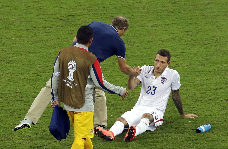 Photo - United States' Fabian Johnson, right, shakes hand with head coach Juergen Klinsmann after a 2-2 draw in the group G World Cup soccer match between the USA and Portugal at the Arena da Amazonia in Manaus, Brazil, Sunday, June 22, 2014. (AP Photo/Themba Hadebe)
