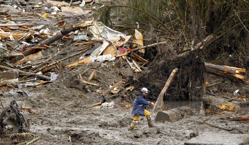 Photo - A searcher walks through mud near a massive pile of debris at the scene of a deadly mudslide, Thursday, March 27, 2014, in Oso, Wash. The death toll is expected to rise considerably within the next two days as the Snohomish County Medical Examiner's Office catches up with the recovery effort, Snohomish County District 21 Fire Chief Travis Hots said Thursday. (AP Photo/The Herald, Mark Mulligan, Pool)