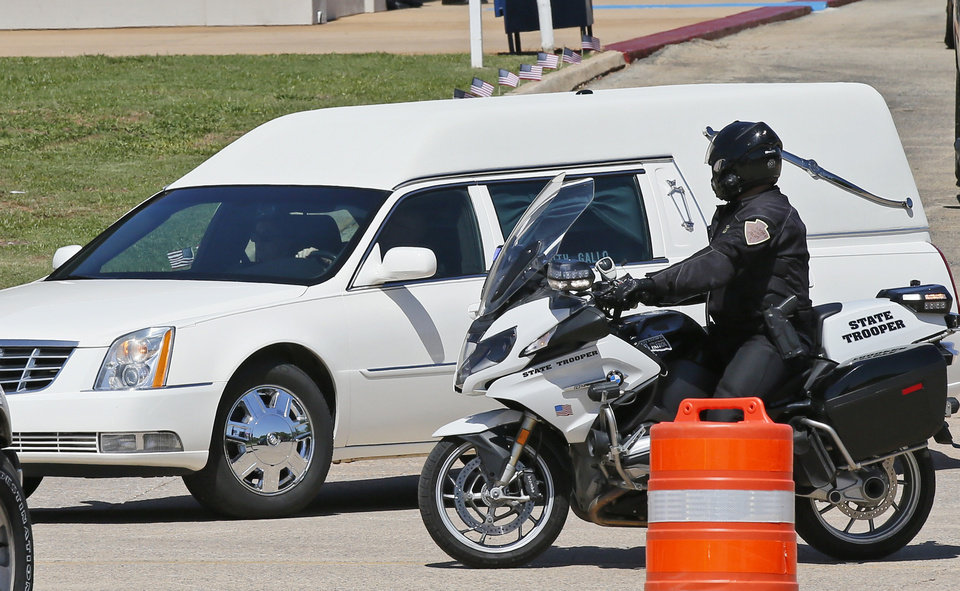 Photo - The hearse carrying the casket of Logan County Deputy David Wade leaves with a motorcycle escort following his funeral in Guthrie, Okla., Monday, April 24, 2017. Wade was shot and killed while serving an eviction notice near Mulhall, Okla,. April 18, 2017. (AP Photo/Sue Ogrocki)