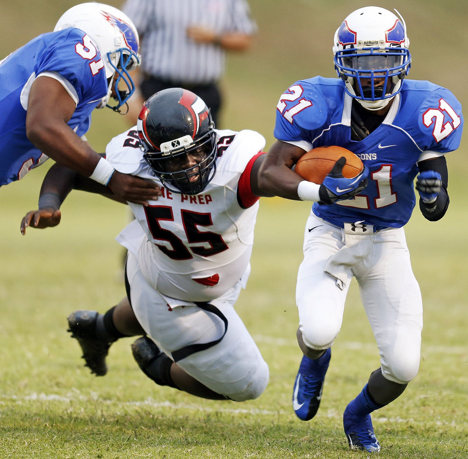 Millwood\'s Janari Glover (21) carries the ball as Stanford Rice (51) blocks Prime Prep\'s Devonte Elder (55) during a high school football game between Millwood and Prime Prep Academy in Oklahoma City, Friday, Sept. 14, 2012. Photo by Nate Billings, The Oklahoman