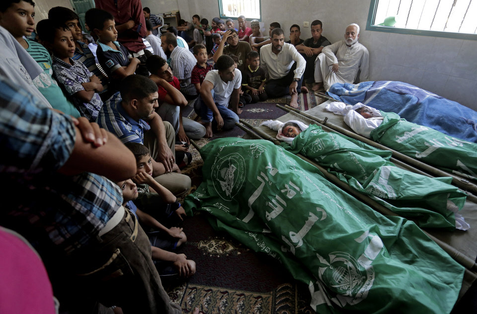 Photo - Palestinians mourn during the funeral of members of the al-Louh family who were killed in an Israeli strike on their home in Deir el-Balah, in the central Gaza Strip, Wednesday, Aug. 20, 2014. Many were killed in an airstrike on the house of the al-Louh family in Deir el-Balah, including a mother, father, three children, and two brothers of the father, according to Gaza health official Ashraf al-Kidra. (AP Photo/Adel Hana)
