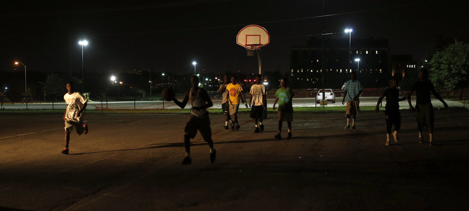 Photo - One shop light illuminates the basketball court as the ball is in bounded during midnight basketball at Christ Temple Community Church in Oklahoma City, Friday, July 25, 2014. Photo by Sarah Phipps, The Oklahoman