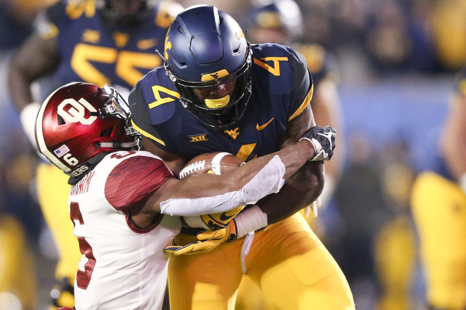 Photo - Oklahoma Sooners cornerback Tre Brown (6) tackles West Virginia Mountaineers running back Leddie Brown (4) during the NCAA football game between the Oklahoma Sooners and the West Virginia Mountaineers at Mountaineer Field at Milan Puskar Stadium in Morgantown, W.Va on Friday, November 23, 2018. IAN MAULE/Tulsa World
