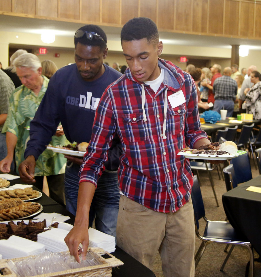 Edmond employee John Byron, left, and, his son, Stephen, go through the buffet line at an appreciation dinner hosted by the city staff.