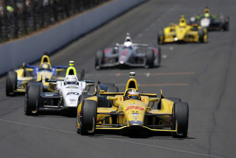 Photo - Ryan Hunter-Reay leads Ed Carpenter into the first turn during the 98th running of the Indianapolis 500 IndyCar auto race at the Indianapolis Motor Speedway in Indianapolis, Sunday, May 25, 2014. (AP Photo/Darron Cummings)