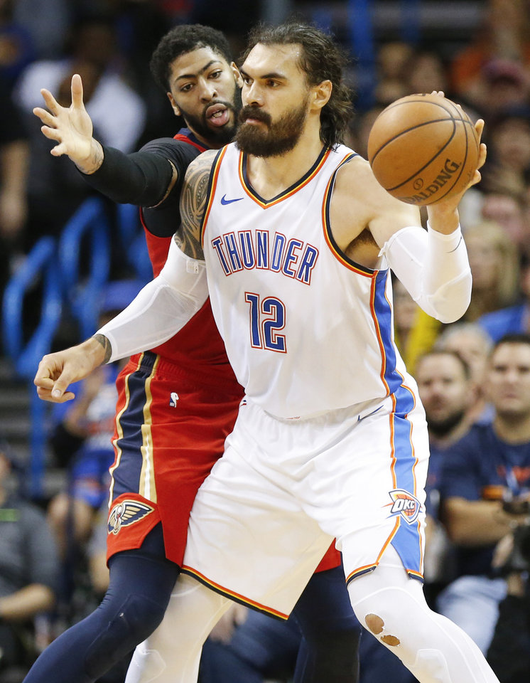 Photo - Oklahoma City's Steven Adams (12) passes away from New Orleans' Anthony Davis (23) during an NBA basketball game between the Oklahoma City Thunder and the New Orleans Pelicans at Chesapeake Energy Arena in Oklahoma City, Monday, Nov. 5, 2018. Oklahoma City won 122-116. Photo by Nate Billings, The Oklahoman