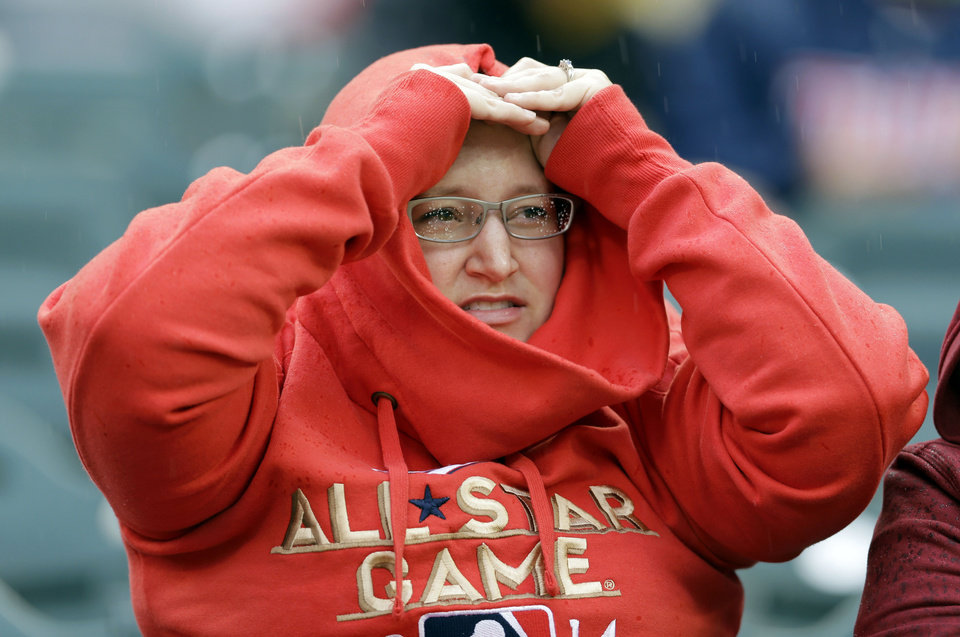 Photo - A fan watches in the rain during National League batting practice for the MLB All-Star baseball game, Monday, July 14, 2014, in Minneapolis. (AP Photo/Jeff Roberson)