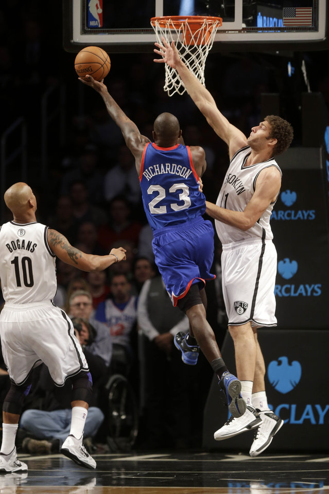 Philadelphia 76ers' Jason Richardson, center, puts up a shot past Brooklyn Nets' Brook Lopez, right, and Keith Bogans during the first half of an NBA basketball game at the Barclays Center Sunday, Dec. 23, 2012 in New York.  (AP Photo/Seth Wenig)