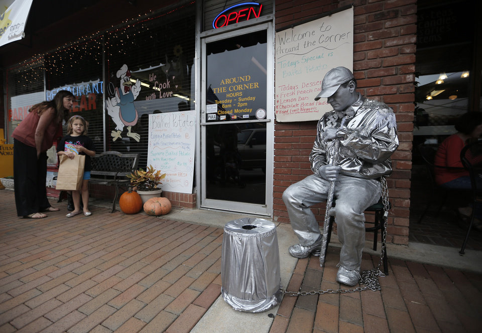 Parents and children observe the silver man during the Downtown Edmond Fall Art Crawl in Edmond, Okla., Saturday, Sept. 29, 2012.  Photo by Garett Fisbeck, The Oklahoman