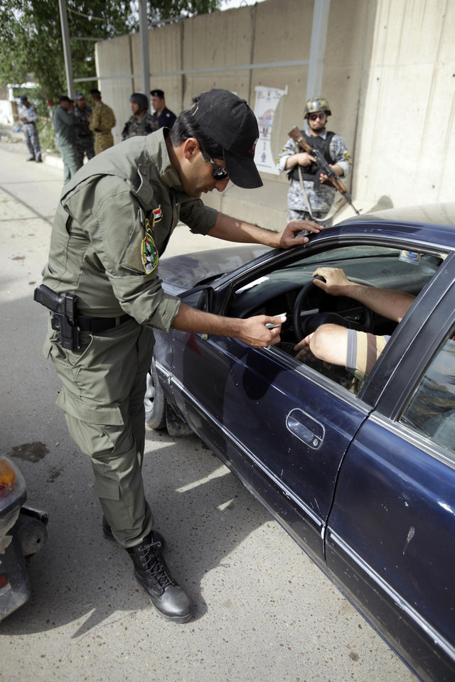 Photo - Iraqi police officers are seen at a checkpoint in central Baghdad, Iraq, Monday, May 2, 2011. Iraqi government has tightened its security measures after the killing of Osama bin Laden. (AP Photo/Karim Kadim)   ORG XMIT: BAG109