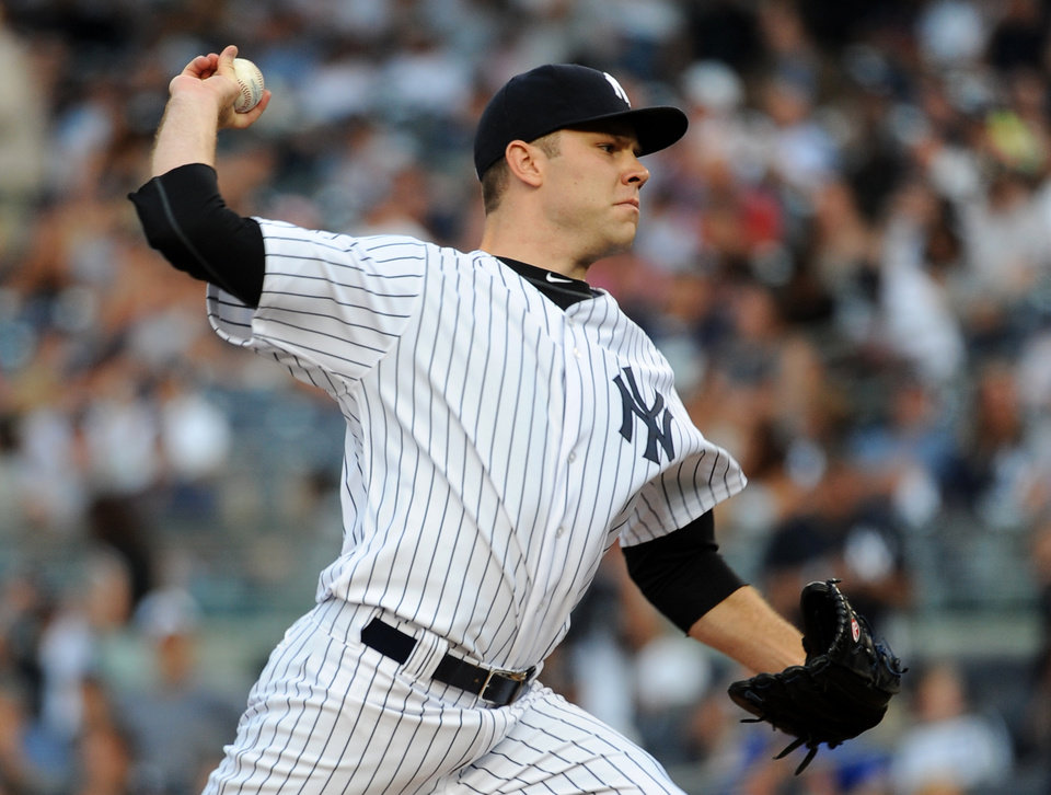 Photo - New York Yankees starter David Phelps pitches against the Cincinnati Reds in the first inning of an interleague baseball game at Yankee Stadium on Friday, July 18, 2014, in New York. (AP Photo/Kathy Kmonicek)