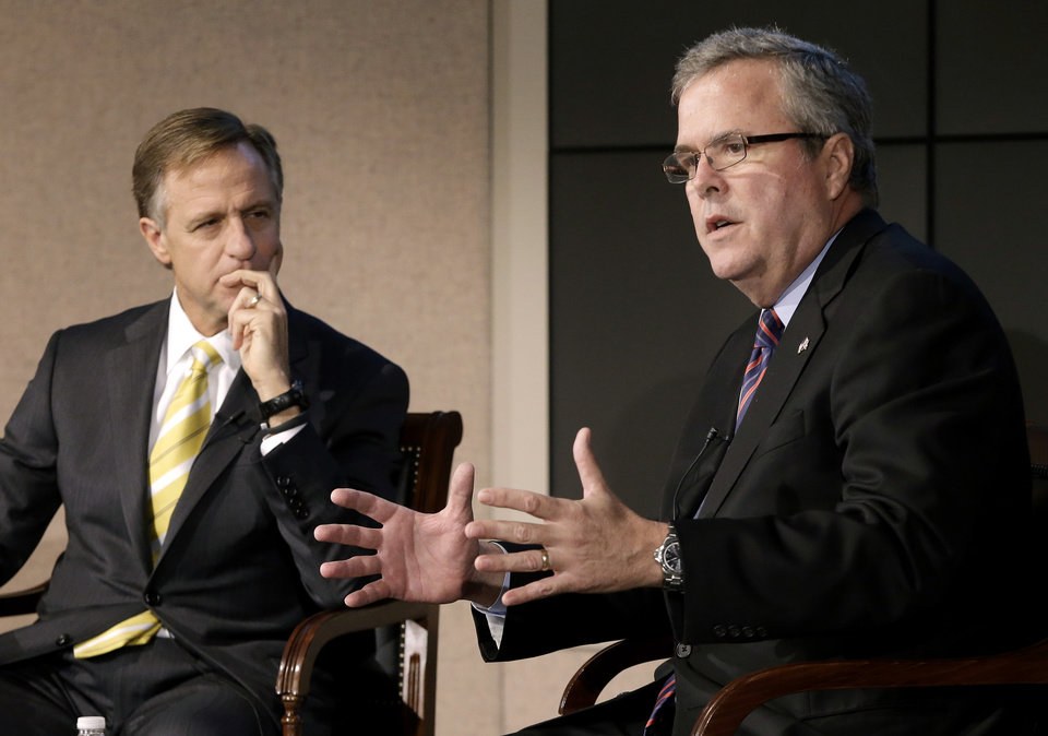 Photo - FILE - This Jan. 14, 2013 file photo shows former Florida Gov. Jeb Bush, right, and Tennessee Gov. Bill Haslam talking about education reform during a forum in Nashville, Tenn. More than five years after governors from both major parties began a mostly quiet effort to set new standards in American schools, the so-called Common Core initiative has morphed into a political tempest that fuels division among Republicans. Bush hails Common Core as a way to improve student performance and, over the long term, competitiveness of American workers. (AP Photo/Mark Humphrey, File)