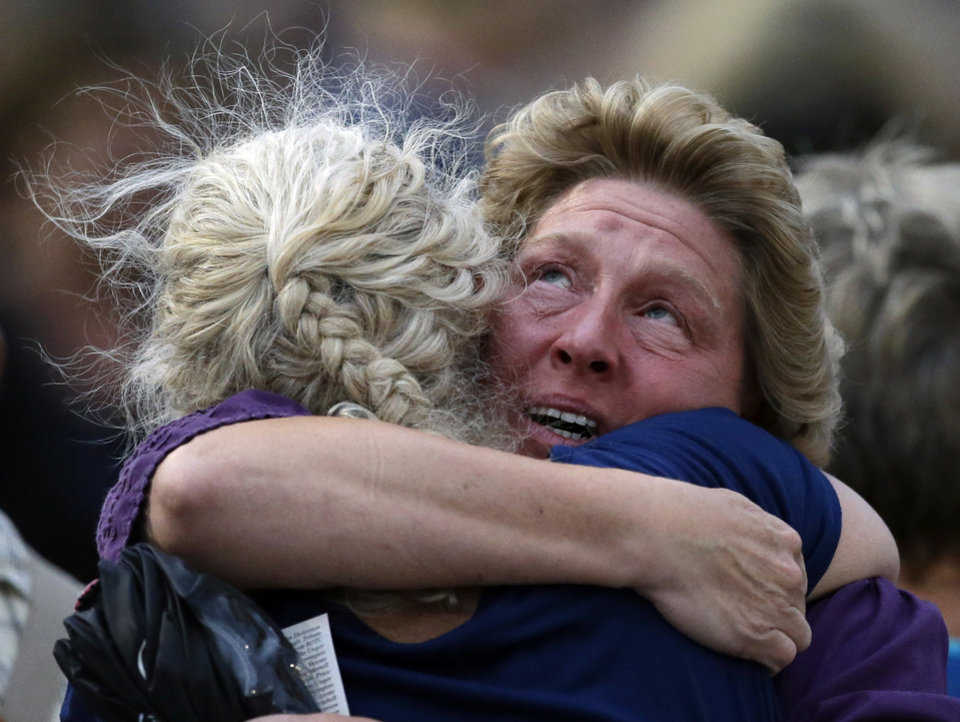 Photo - Family members hug during a community vigil on Tuesday, July 2, 2013, in Prescott, Ariz. for the 19 firefighters from Granite Mountain Interagency Hotshot Crew that were killed battling a wildfire near Yarnell, Ariz. The elite crew of firefighters were overtaken by the out-of-control blaze as they tried to protect themselves from the flames under fire-resistant shields on Sunday. (AP Photo/Chris Carlson)