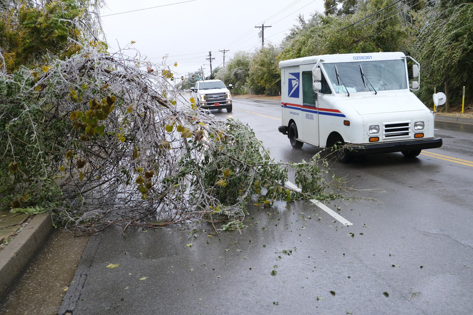 Photo - Traffic drives around fallen branch on 15th St. east of Boulevard from the ice storm that hit the Oklahoma City metro area Tuesday, October 27, 2020. [Doug Hoke/The Oklahoman]