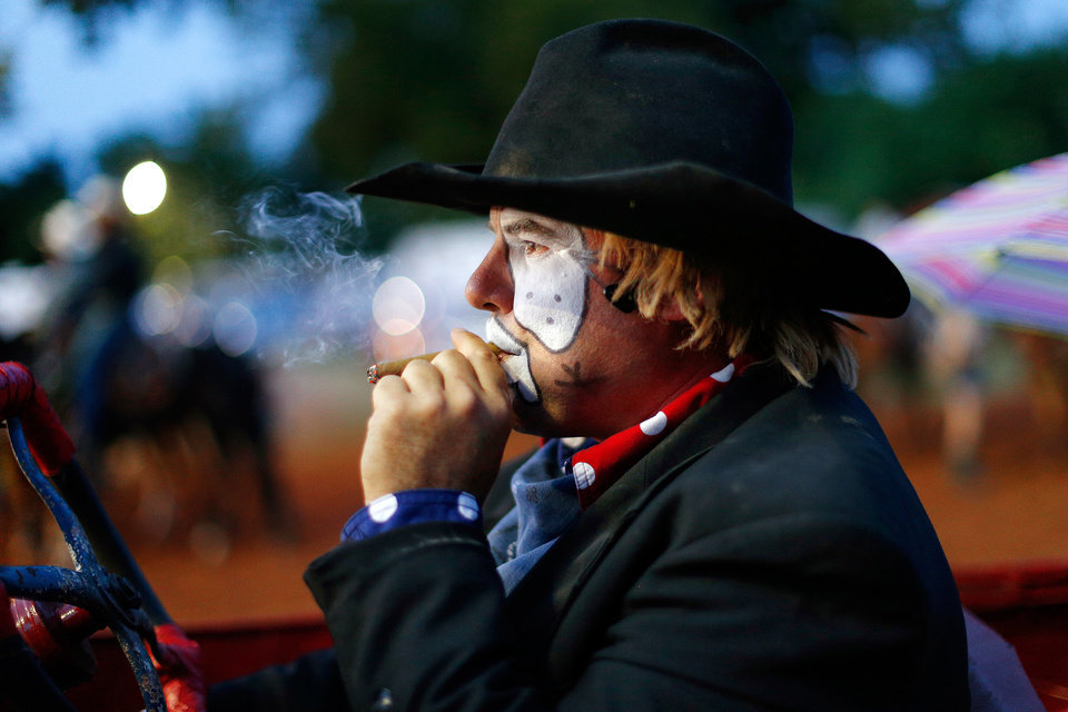 Photo -  Second-generation rodeo barrel man Shane Parli smokes a cigar that he uses in his show as he waits to perform during the LibertyFest Rodeo in Edmond, Okla., Saturday, June, 22, 2013.