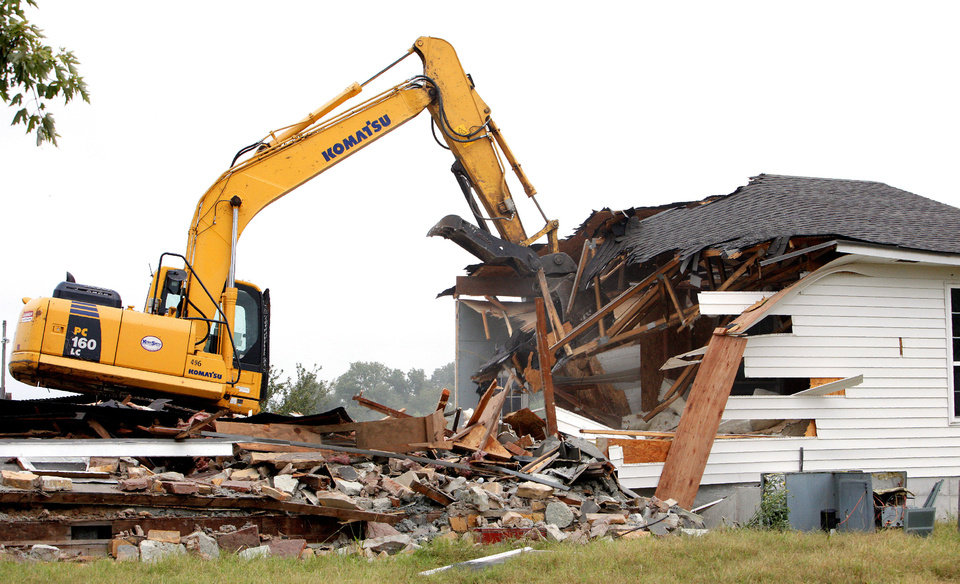 Photo - A track hoe demolishes the home of Gary and Rhonda Buford on Triple X Road at NE 36 Street in Choctaw on Wednesday. The Bufords and their adult son were forced from their property last June after flooding caused the North Canadian River to change course.  Photo by Paul B. Southerland, The Oklahoman  PAUL B. SOUTHERLAND