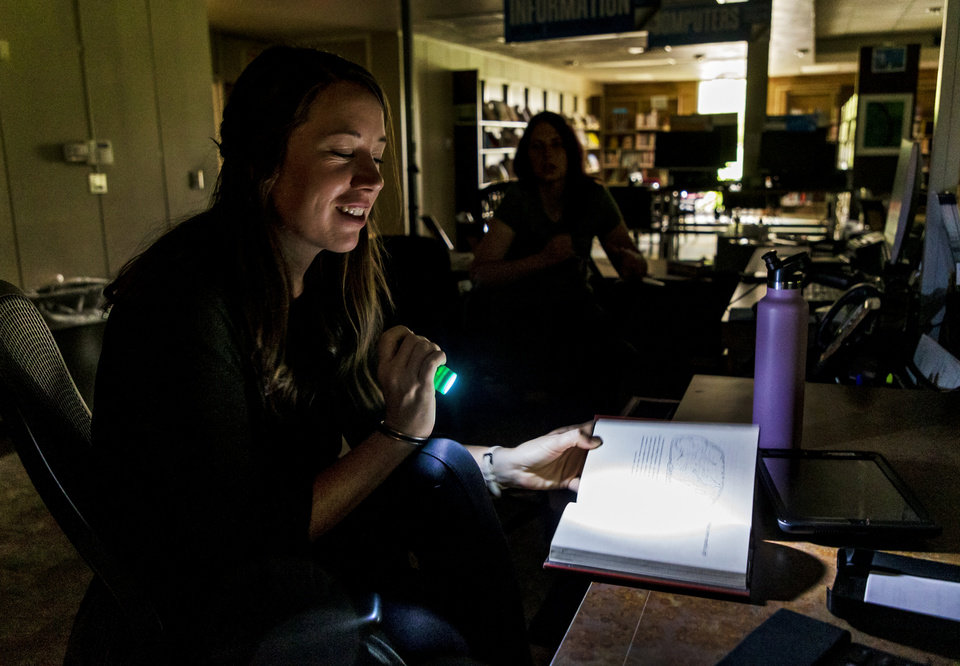 Photo - Shelbie Marks and Crystal Easley, from left, use flashlights to work in the dark as they operate the Del City Library in Del City, Okla. on Tuesday, Aug. 27, 2019. Strong storms knocked out power, and caused damage in the area overnight. [Chris Landsberger/The Oklahoman]