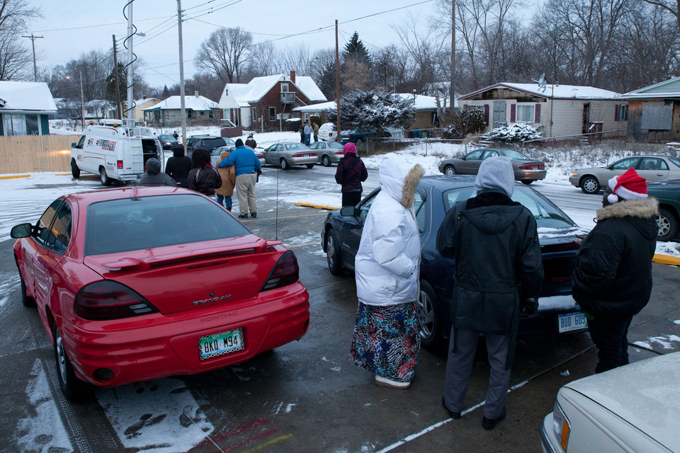 Photo - Friends and family members gather outside the home where two parents were found dead, Tuesday, Dec. 25, 2012 in Flint, Mich. Authorities say five people are dead in two separate incidents of what is believed to be accidental carbon monoxide poisoning. (AP Photo/Flint Journal, Griffin Moores)