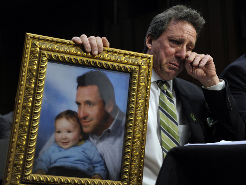 Photo - Neil Heslin, the father of a six-year-old boy who was slain in the Sandy Hook massacre in Newtown, Conn., on Dec. 14, holds a picture of himself with his son Jesse and wipes his eye while testifying on Capitol Hill in Washington, Wednesday, Feb. 27, 2013, before the Senate Judiciary Committee on the Assault Weapons Ban of 2013. (AP Photo/Susan Walsh)