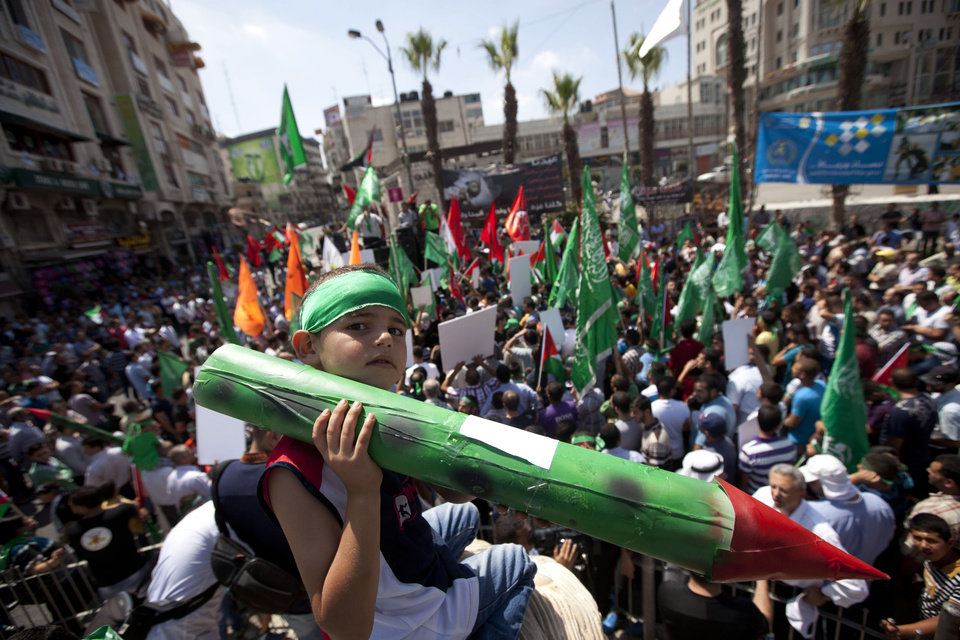 Photo - A Palestinian boy, along with supporters of Hamas, holds a representation of a rocket as others shout slogans to protest against Israel and to support people in Gaza, during a demonstration in the West Bank city of Ramallah, Friday, Aug. 22, 2014. (AP Photo/Majdi Mohammed)