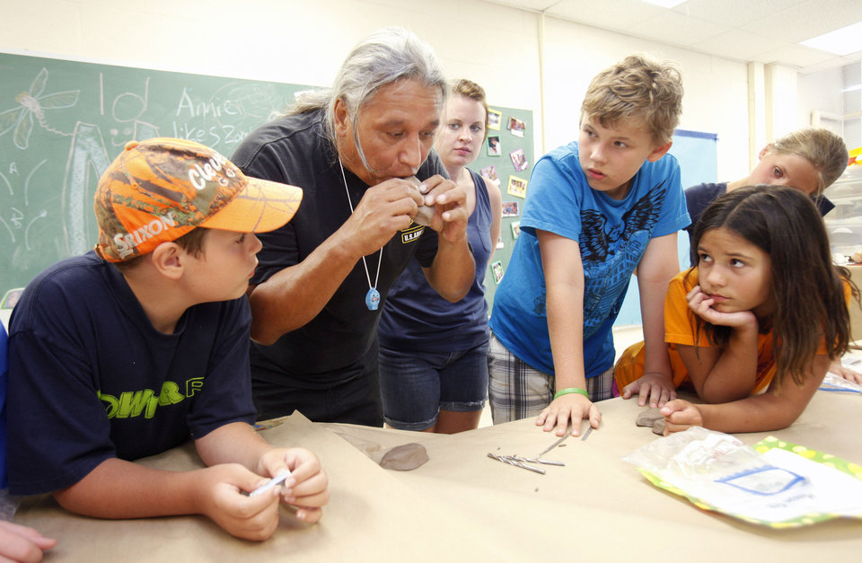 Photo - Albert Grayeagle and campers at Camp Chaverim work to create clay flutes Tuesday at the summer camp sponsored by the Jewish Federation of Greater Oklahoma City. Photos by PAUL HELLSTERN, The Oklahoman