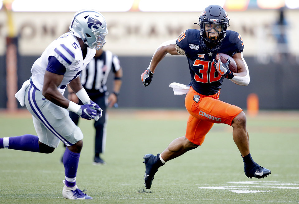 Photo - Oklahoma State's Chuba Hubbard (30) looks to get by Kansas State's Da'Quan Patton (5) during the college football game between the Oklahoma State Cowboys and the Kansas State Wildcats at Boone Pickens Stadium in Stillwater, Okla., Friday, Sept. 27, 2019. [Sarah Phipps/The Oklahoman]