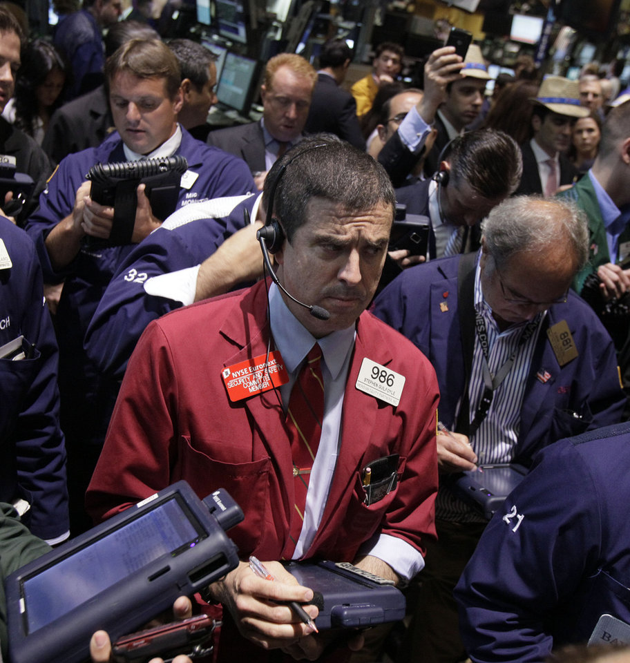 Photo -   FILE - In a June 22, 2012 file photo Trader Stephen Guilfoyle, center, works on the floor of the New York Stock Exchange. Whipsawed by strong earnings from some companies, weak ones from others, including the once infallible Apple, investors couldn't make up their mind whether to buy or sell on Wednesday July 25, 2012. (AP Photo/Richard Drew)