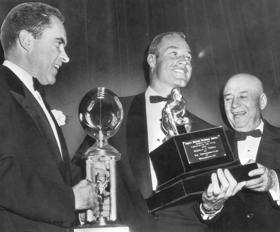 Photo - Sooner center Jerry Tubbs grins in 1957 as he holds the Knute Rockne trophy, presented him as the nation's top college football lineman. House speaker Sam Rayburn (right) made the presentation at the Washington Touchdown club dinner Saturday night. Vice President Richard Nixon (left) then awarded the club's national championship trophy to Tubbs as captain of the OU team.