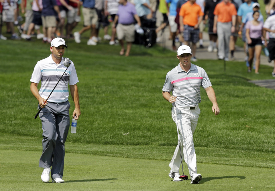 Photo - Sergio Garcia, left, and Rory McIlroy walk up the second fairway during the final round of the Bridgestone Invitational golf tournament Sunday, Aug. 3, 2014, at Firestone Country Club in Akron, Ohio. (AP Photo/Mark Duncan)