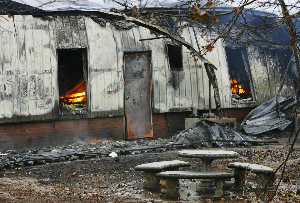 Photo - ICE STORM: Flames can be seen inside classrooms more than six hours after the fire started at Jones High School  Monday morning, Dec. 10,  2007.  By Jim Beckel, The Oklahoman. ORG XMIT: KOD