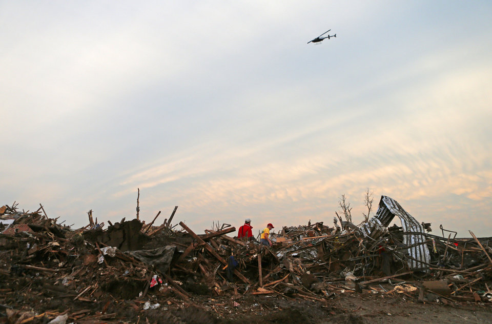 A helicopter flies over a residential area near Plaza Towers Elementary School Preston, left, in Moore, Okla., after a tornado moved through the area on Monday, May 20, 2013. Photo by Bryan Terry, The Oklahoman