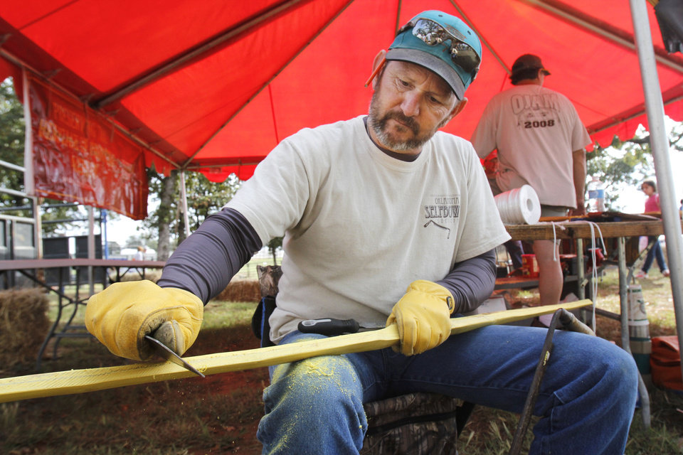 Photo - Rodney Wilson demonstrates how to make a bow from a piece of Osage Orange wood during school day of the Oklahoma Wildlife Expo at the Lazy E Arena and Ranch in Guthrie, OK, Friday, September 28, 2012,  By Paul Hellstern, The Oklahoman