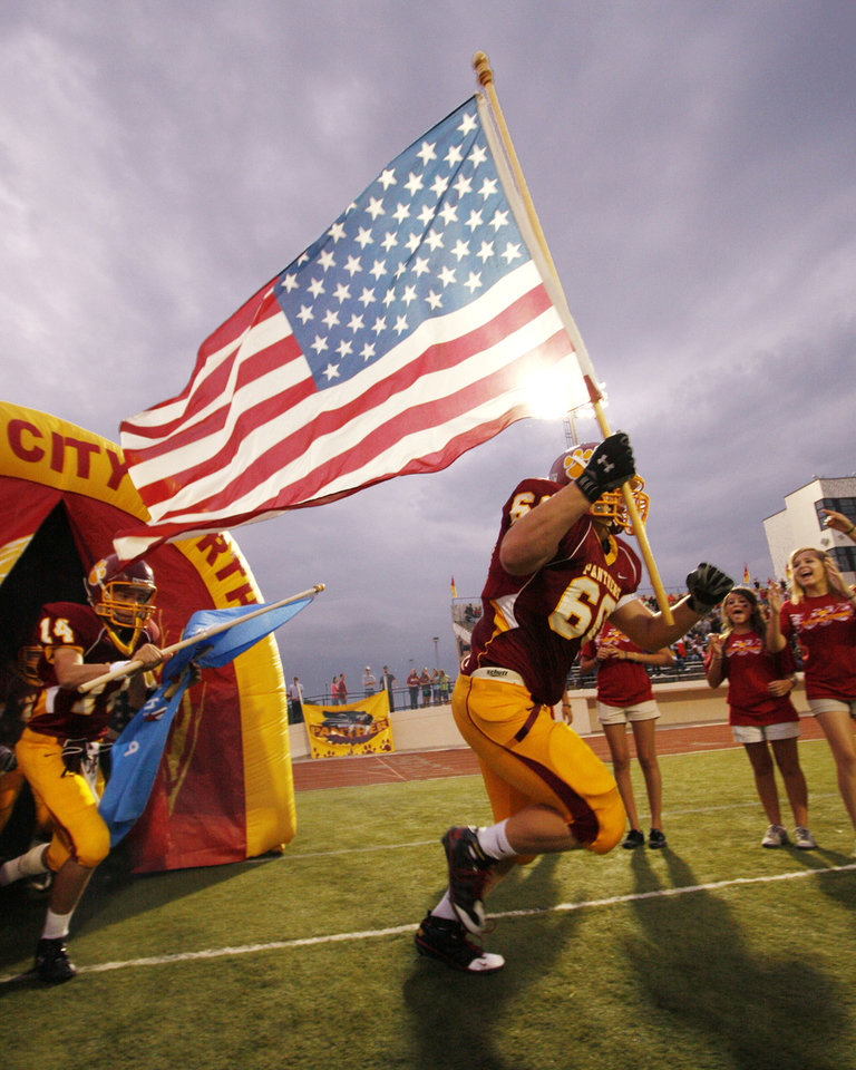 Photo - 911 / 9/11 / TERRORISM / TERRORIST ATTACK ON AMERICA / WORLD TRADE CENTER / TOWERS / PENTAGON / PLANE CRASH: Putnam City North High School football player Dustin Decker runs onto the field carrying a flag on Sept. 11 in honor of those who died in the attacks. MANDATORY CREDIT:  PHOTO BY RICHARD T. CLIFTON ORG XMIT: KOD