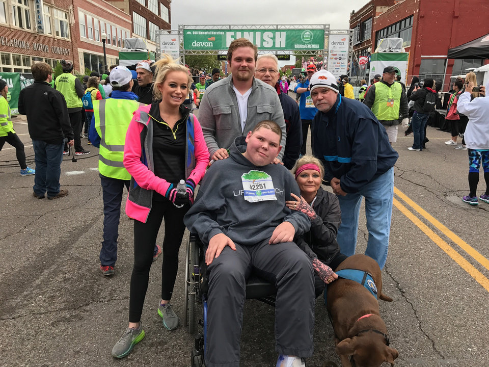 Photo -  Austin Varnum, center, with his family and his guide dog, Sugar, after completing the 5K at the Oklahoma City Memorial Marathon on Sunday. [PHOTO BY JACOB UNRUH, THE OKLAHOMAN]