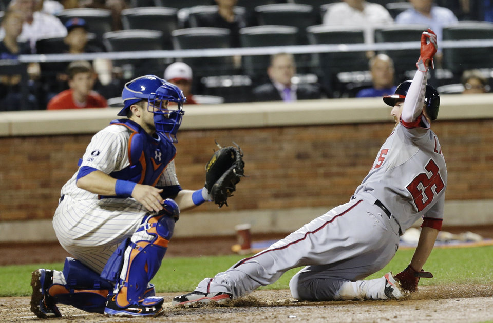 Photo - Washington Nationals first baseman Adam LaRoche (25) slides past New York Mets catcher Travis d'Arnaud to score on a sacrifice fly by Bryce Harper during the seventh inning of a baseball game Wednesday, Aug. 13, 2014, in New York.  (AP Photo/Frank Franklin II)