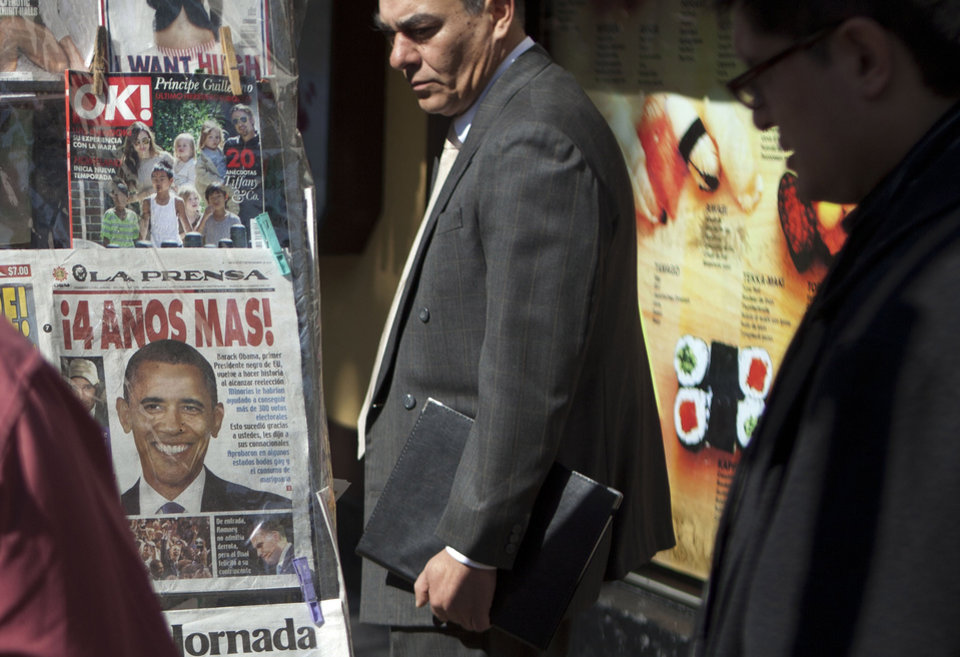 "People look at newspaper for sale at a newsstand, one with a front page showing President Barack Obama with a headline that reads in Spanish ""4 More Years!"" one day after U.S. elections in Mexico City, Wednesday, Nov. 7, 2012. (AP Photo/Eduardo Verdugo)"