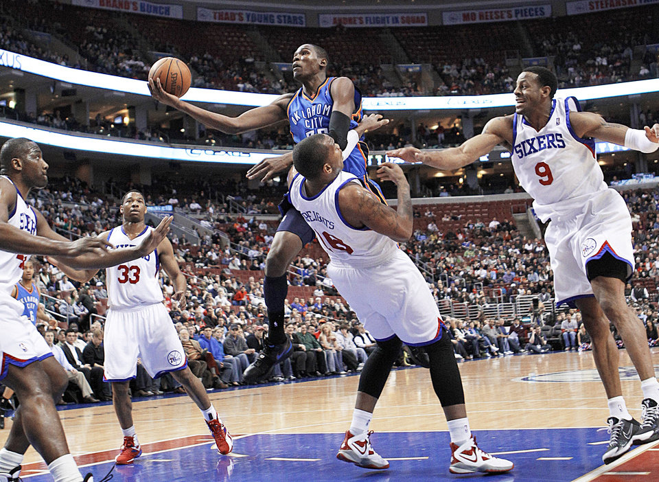 Photo - OKC's Kevin Durant, center, goes up for a shot against, from left, Elton Brand, Willie Green, Marreese Speights and Andre Iguodala of Philadelphia during action on Tuesday. AP photo