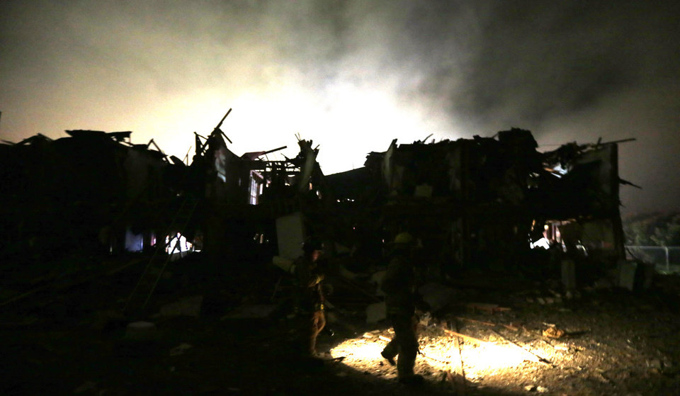 Photo - Firefighters us flashlights to search a destroyed apartment complex near a fertilizer plant that exploded earlier in West, Texas, in this photo made early Thursday morning, April 18, 2013.  (AP Photo/LM Otero)