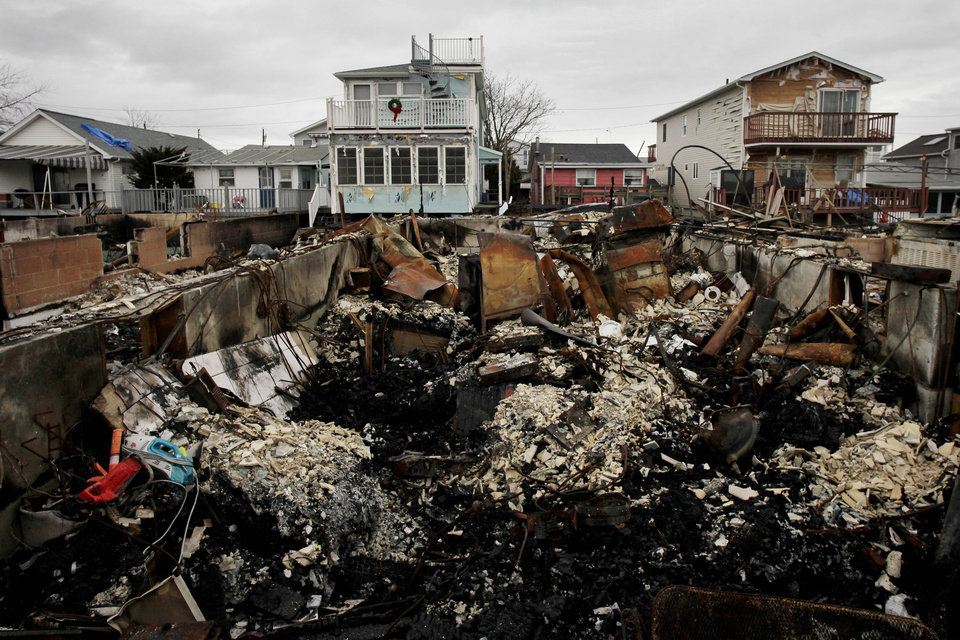 Photo - A Christmas wreath is displayed on the second floor porch railing of a home adjacent to the fire-damaged zone in the Breezy Point section of New York, Friday, Dec. 7, 2012. Over 100 homes were burned to the ground during Superstorm Sandy. (AP Photo/Mark Lennihan)