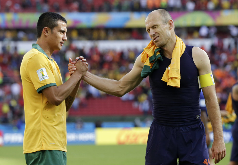 Photo - Netherlands' Arjen Robben, right, shakes hands with Australia's Tim Cahill following the Netherlands' 3-2 victory over Australia during the group B World Cup soccer match between Australia and the Netherlands at the Estadio Beira-Rio in Porto Alegre, Brazil, Wednesday, June 18, 2014. (AP Photo/Fernando Vergara)