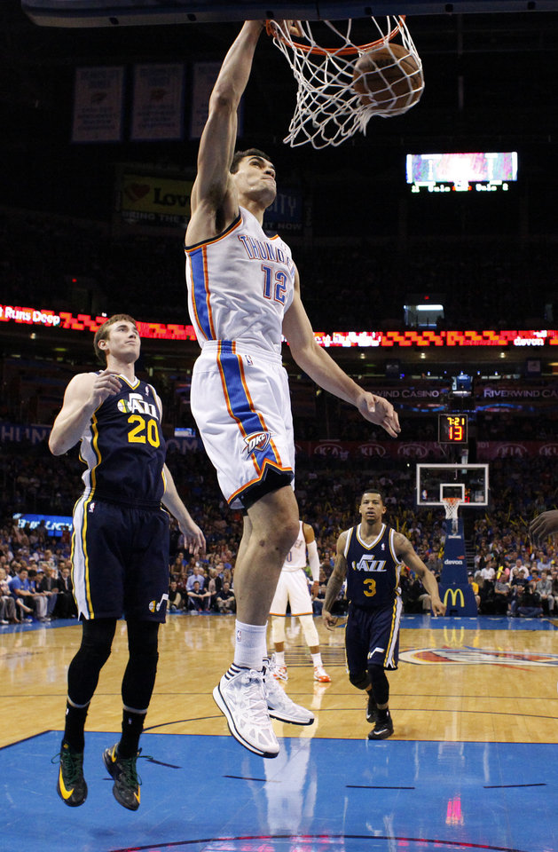 Oklahoma City 's Steven Adams (12) dunks in front of Utah's Gordon Hayward (20)  during the NBA game between the Oklahoma City Thunder and the Utah Jazz at the Chesapeake Energy Arena, Sunday, March 30, 2014, in Oklahoma City. Photo by Sarah Phipps, The Oklahoman