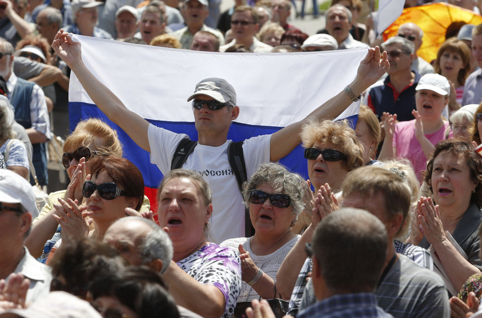 Photo - A man holds a Russian flag during a pro-Russian meeting in the city of Donetsk, eastern Ukraine Sunday, June 22, 2014. Russian President Vladimir Putin publicly expressed support Sunday for Ukraine's declaration of a cease-fire in its battle against pro-Russian separatists and called on both sides to negotiate a compromise.  (AP Photo/Dmitry Lovetsky)