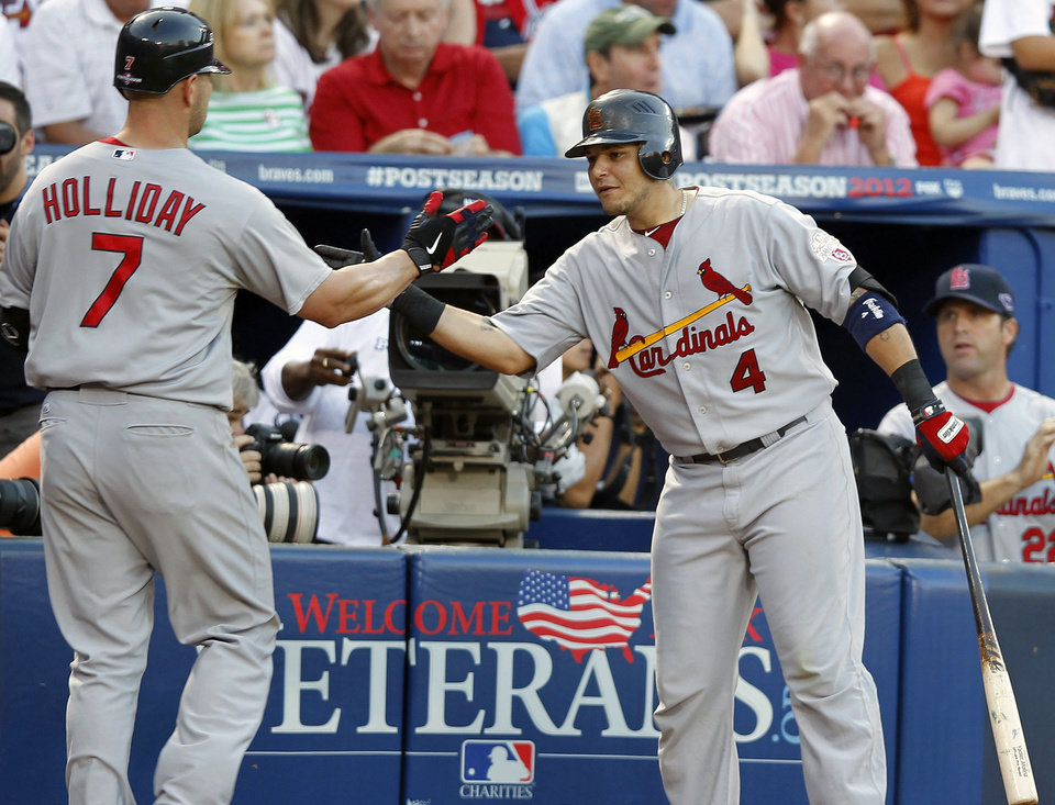 St. Louis Cardinals' Matt Holliday (7) reacts to his solo home run with teammate Yadier Molina (4) during the sixth inning of the National League wild card playoff baseball game against the Atlanta Braves, Friday, Oct. 5, 2012, in Atlanta. (AP Photo/John Bazemore)