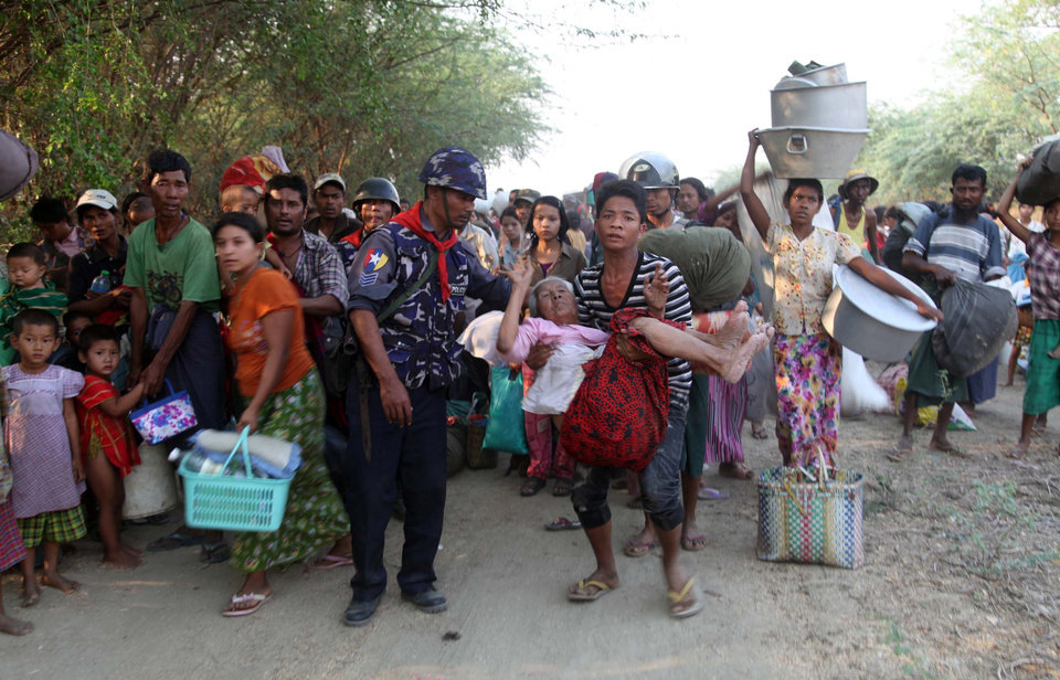 Myanmar police helps Muslims refugees to move a rescue camp in Meikhtila  about 550 kilometers (340 miles) north of Yangon, Myanmar, Friday, March 22, 2013.  Myanmar's president declared a state of emergency Friday in a central city shaken by sectarian bloodshed that has killed at least 20 people, as thousands of minority Muslims fled and overwhelmed riot police crisscrossed the still-burning town seizing machetes and hammers from enraged Buddhist mobs. Black smoke and flames poured from destroyed buildings in Meikhtila, where the unrest between local Buddhist and Muslim residents erupted Wednesday, the latest challenge to Myanmar's ever-precarious transition to democratic rule.(AP Photo/Khin Maung Win)